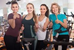 Fêmeas satisfeitas do treinamento diferente da idade em bicicletas de exercício Imagens de Stock Royalty Free