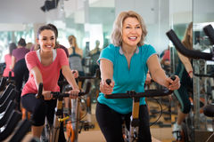 Fêmeas vigorosas do treinamento diferente da idade em bicicletas de exercício Fotografia de Stock Royalty Free