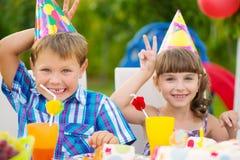 Fête d'anniversaire avec le gâteau coloré à l'arrière-cour Photo stock