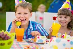 Fête d'anniversaire avec le gâteau coloré à l'arrière-cour Image libre de droits