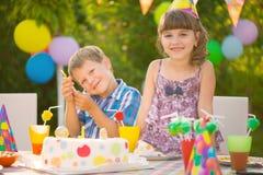 Fête d'anniversaire avec le gâteau coloré à l'arrière-cour Images stock