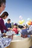 Fête d'anniversaire, famille sur plusieurs générations, apportant le gâteau à la table Photographie stock libre de droits