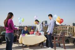 Fête d'anniversaire, famille sur plusieurs générations s'asseyant à la table Photographie stock