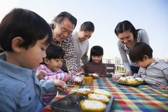 Fête d'anniversaire, famille sur plusieurs générations, s'asseyant à la table Photos stock