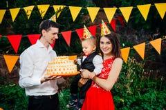 Fête d'anniversaire, nourriture et bonbons soumis du ` s d'enfants Une jeune famille célèbre un an de fils Le papa tient un grand Photos libres de droits