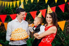 Fête d'anniversaire, nourriture et bonbons soumis du ` s d'enfants Une jeune famille célèbre un an de fils Le papa tient un grand Photo libre de droits