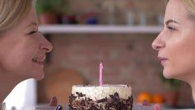 Fête des mères, fille avec la maman soufflant la bougie sur le gâteau et souriant étroitement