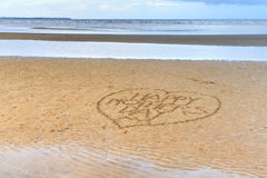 Le jour de mère heureux écrit dans le sable Images stock