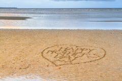 Le jour de mère heureux écrit dans le sable Photos stock