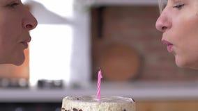 Fête des mères heureuse, fille avec la maman soufflant la bougie sur le gâteau et souriant étroitement