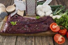 Fígado cru com vegetais e cutelaria Fotos de Stock