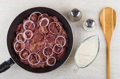 Fígado de galinha com cebola, sal, pimenta, colher e creme de leite Foto de Stock