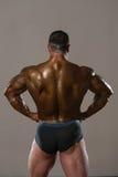 Físicamente hombre que muestra su parte posterior bien entrenada Imagen de archivo libre de regalías