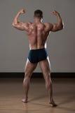 Físicamente hombre que muestra su parte posterior bien entrenada Foto de archivo