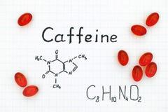 Fórmula química da cafeína com comprimidos vermelhos imagem de stock