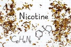 Fórmula química de la nicotina con el tabaco derramado fotos de archivo libres de regalías