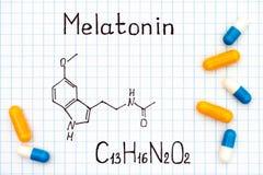 Fórmula química del Melatonin con algunas píldoras imagen de archivo