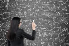 Fórmulas de la escritura de la mujer en la pizarra Imagen de archivo