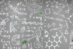 Fórmulas químicas dibujadas en la pared gris fotos de archivo
