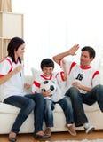 Fósforo de futebol de observação da família alegre Imagens de Stock Royalty Free