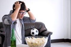 Fósforo de futebol de observação do fanclub asiático novo do homem na tevê e em cheering imagens de stock