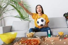 Fósforo de observação do aficionado desportivo da jovem mulher em uma gritaria amarela do t-shirt irritada fotografia de stock
