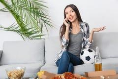 Fósforo de observação do aficionado desportivo da jovem mulher que fala usando o smartphone imagem de stock