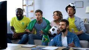 Fósforo de observação dos amigos brasileiros em casa, apoiando a equipe de futebol nacional fotografia de stock royalty free