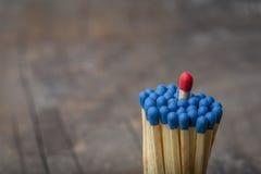 Fósforo vermelho no grupo de fósforos azuis Imagens de Stock Royalty Free