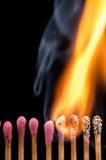 Fósforos ardentes em uma linha Fotografia de Stock