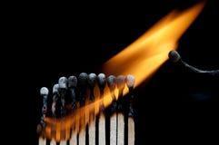 Fósforos ardentes no preto Imagens de Stock