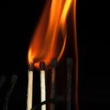 Fósforos ardentes no preto Imagem de Stock Royalty Free