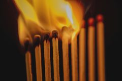 Fósforos de queimadura contra a obscuridade fotografia de stock royalty free