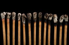 Fósforos novos e queimados, close-up, fundo preto Fotos de Stock Royalty Free