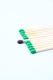 Fósforos verdes com o fósforo queimado que fura para fora Fotografia de Stock