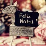Födelse- ren- och textfeliz, glad jul i portugis Royaltyfri Bild