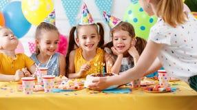 Födelsedag för barn` s lyckliga ungar med kakan Arkivfoton