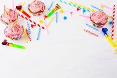 Födelsedagbakgrund med rosa muffin och stearinljus Arkivbilder