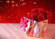 Födelsedagbegrepp med röda rosor i gåva på träskrivbordet elfte 11th 3d framför Arkivfoto