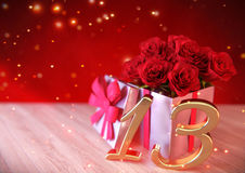 Födelsedagbegrepp med röda rosor i gåva på träskrivbordet trettonde 13th 3d framför Arkivbilder