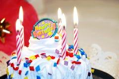 födelsedagcaken undersöker lyckligt Royaltyfri Bild