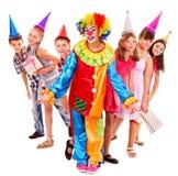 Födelsedagdeltagaregrupp av teen med clownen. Arkivfoton