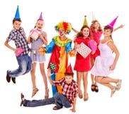 Födelsedagdeltagaregrupp av teen med clownen. Arkivbilder