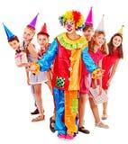 Födelsedagdeltagaregrupp av teen med clownen. Arkivbild