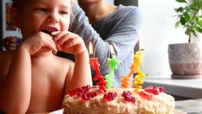 Födelsedagen av lilla flickan blåser hon ut stearinljus på kakan arkivfilmer