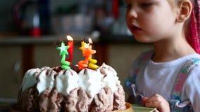 Födelsedagen av lilla flickan blåser hon ut stearinljus på kakan stock video