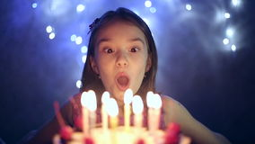 Födelsedagen av lilla flickan blåser hon ut stearinljus på kakan långsam rörelse