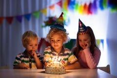 födelsedagen lurar deltagaren Stearinljus för barnslagkaka arkivbild