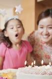Födelsedagflicka omkring som ut blåser henne stearinljus Royaltyfri Fotografi