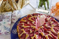 Födelsedagjordgubbekaka och gåvor på den vita bordduken Fotografering för Bildbyråer